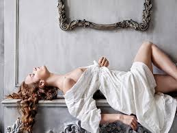 bare breast woman with bare breast in a white baroque dress lying on the