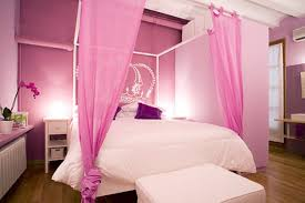 white bed cover on the bed and pink fabric curtains connected by