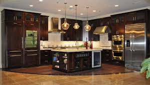 beige paint colors in kitchen with dark stained cabinets with granite countertops with glass pendant lighting fixtures