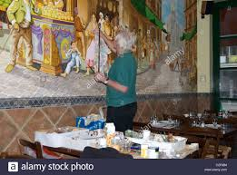 artist painting mural on the wall of an italian restaurant notting artist painting mural on the wall of an italian restaurant notting hill london uk