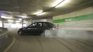 driver drifts a bmw up the ramp of a parking garage