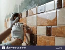 Installing Ceramic Wall Tile Laying Ceramic Tiles Tiler Placing Ceramic Wall Tile In Position