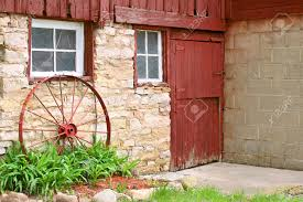 Red Barn Door by An Antique Metal Wagon Wheel Is Leaning Up Against An Old Stone