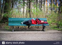bench berlin homeless man sleeping on park bench in berlin stock photo