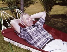 1960s older man lying in hammock in backyard retired lifestyle