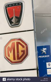 peugeot car symbol rover peugeot and mg car makers symbols on garage forecourt stock