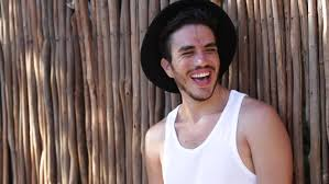 young hipster man laughing relaxed in front of the camera stock