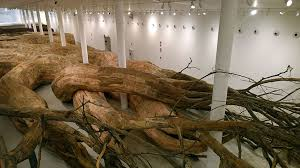 artist uses repurposed wood to build root like tunnels you