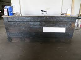 reception desk made from railroad ties with a sign plate on front