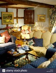cream sofa and blue armchairs in cluttered cottage living room