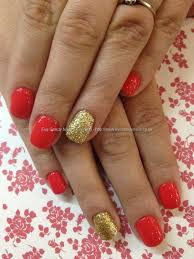 coral polish with gold glitter ring finger over acrylic nails