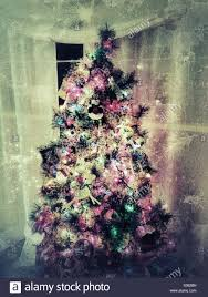 grungy christmas tree with bright lights and ornaments in the