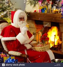mr santa claus eating cookies by fireplace stock photo royalty