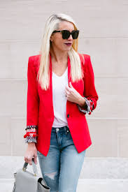 red blazer with embellished cuffed sleeves worn with distressed jeans