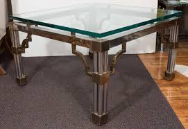 asian inspired glass top chrome coffee table with brass detail for
