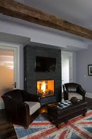 this dark stone mantle contains a roaring fire for a peaceful reading area a television