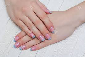 french nail art in light blue color on wooden background stock