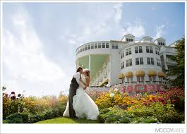 island wedding photographers and groom on mackinac island in front of grand hotel image