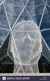 sculpture of a human head in front of a modern building of windows sculpture of a human head in front of a modern building of windows calgary alberta canada