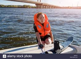young fit woman ready to ride water skis siting on the boat