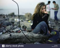 young female sitting on dirty beach biting nails two people