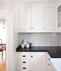 white cabinets with black countertops and backsplash marble herringbone backsplash tile with black granite