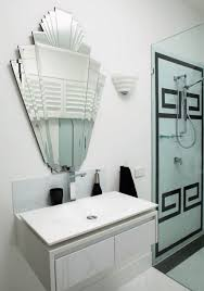 art deco bathroom with art deco tiles and mirror also wall sconce