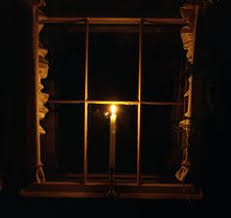 winter solstice candle in the window looking through windows