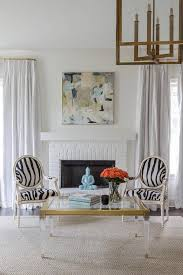 white brick fireplace with black and white zebra chairs