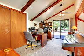 loft office room with ceiling beams and carpet floor furnished