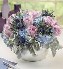 silver vase of blue and purple flowers centerpiece flower