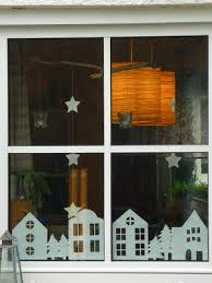 paper cutouts of houses trees stars for winter window