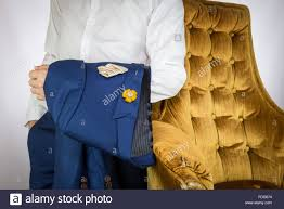 man carries blue suit standing beside yellow cozy sofa stock photo