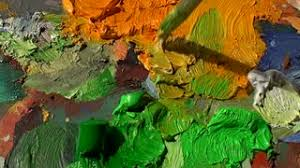 professional painter mixing colors on a palette with oil paint