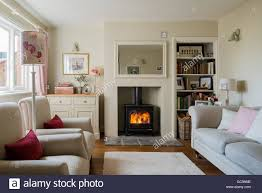 cosy cottage sitting room with wood burning stove and linen stock