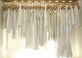line of new white clothes hanging on wooden hangers in a fashion
