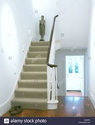 Asian Wooden Floor Asian Statue At The Bend Of Staircase With Beige Carpet In White