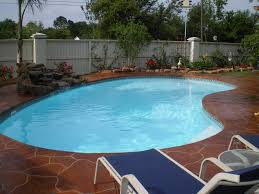 small kidney shaped fiberglass pool with beautiful decking this