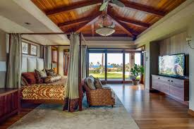 bedroom sloped ceiling with skylight and ceiling beams in bedroom