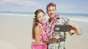 Hawaii travel man images Couple on beach taking selfie with smartphone young woman and man jpg