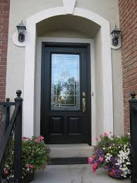 glass and black wooden entry doors connected by double black wall