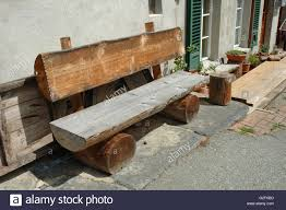 old wooden bench made of tree trunk standing at building wall