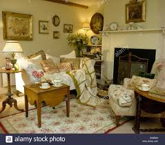 cushions and throw on white sofa in cottage living room with rose cushions and throw on white sofa in cottage living room with rose patterned rug and small