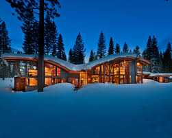 the snow covered exterior of the modern mountain cabin rustic