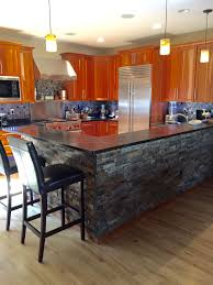 awesome gourmet kitchen with dry stacked stone bar front and glass