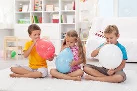 large balloons three kids blowing large balloons sitting on the floor stock photo