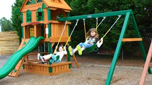 decorating wooden playsets with blue iron swing and wooden wall
