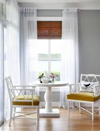 bamboo blinds in the corner window with white sheer curtain