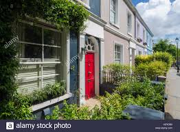 colorful and overgrown house facades with red front door at stock