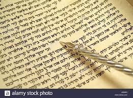torah yad hebrew torah scroll with silver yad pointing to script stock photo